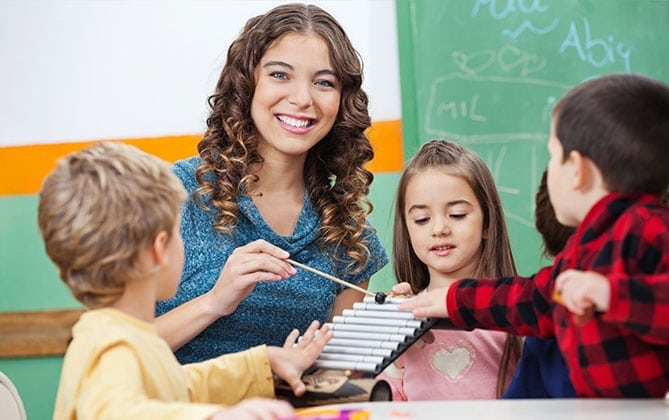 a teacher smiling while teaching music to three children