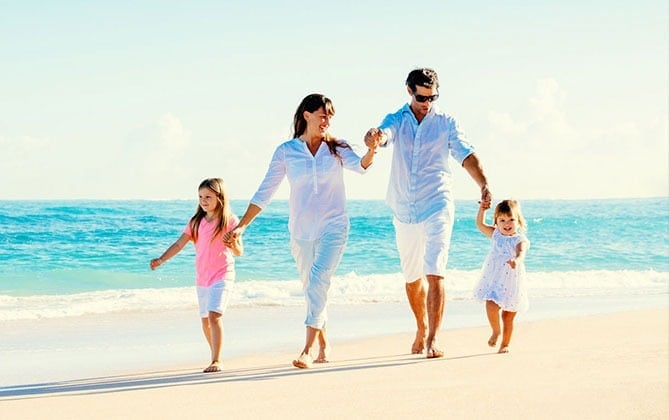 a happy family walking at the beach