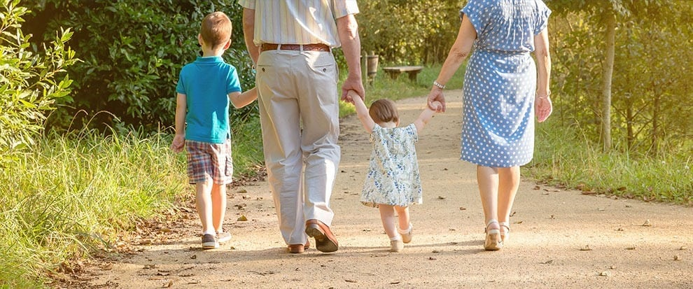 two small children with their grandparents walking on a beautiful road