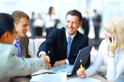 businessman shaking another man's hand when completing a commercial insurance service