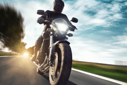 motorcycle insurance from newman represented by a person riding a motorcycle on a road